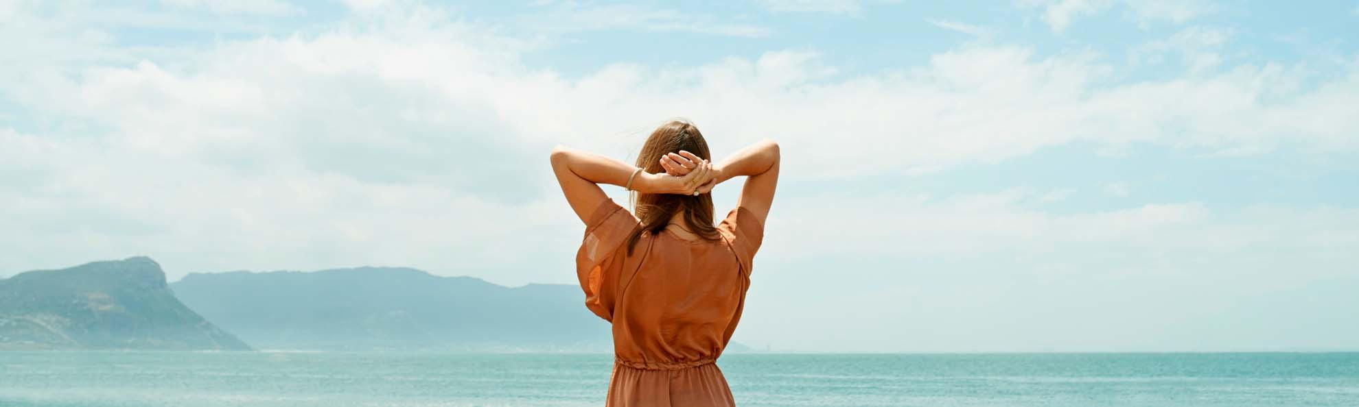 eine frau verschraenkt ihre arme ueber dem kopf und schaut auf das meer und den horizont