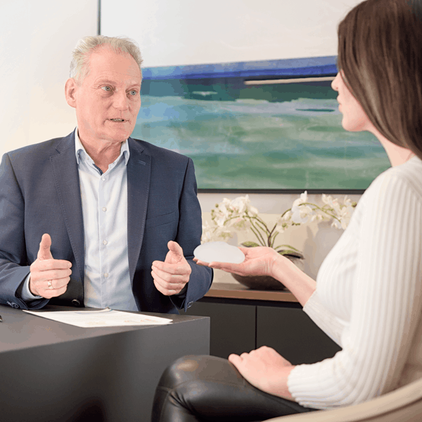 Dr. med. Patrick Bauer Beratungstermin. Dr und Patientin unterhalten sich ueber brustvergroesserung, dabei haelt sie ein Musterimplantat in den haenden